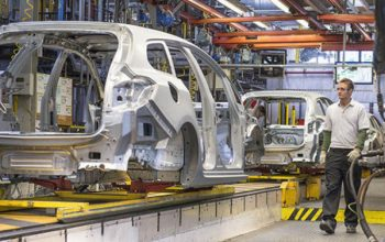 New production line for the assembly of cars with modern equipment and senior mechanical engineer.